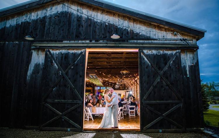 Bride and groom posing between barn doors at Port Farms' wedding reception venue