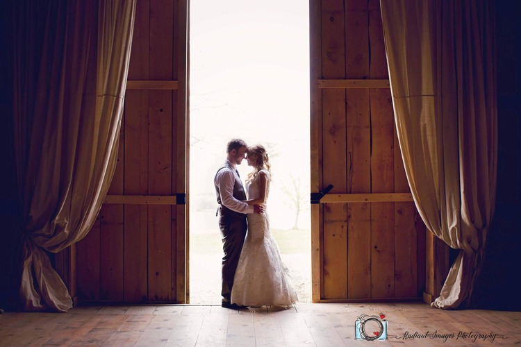 Bride and groom standing in between doors at their barn wedding at Port Farms