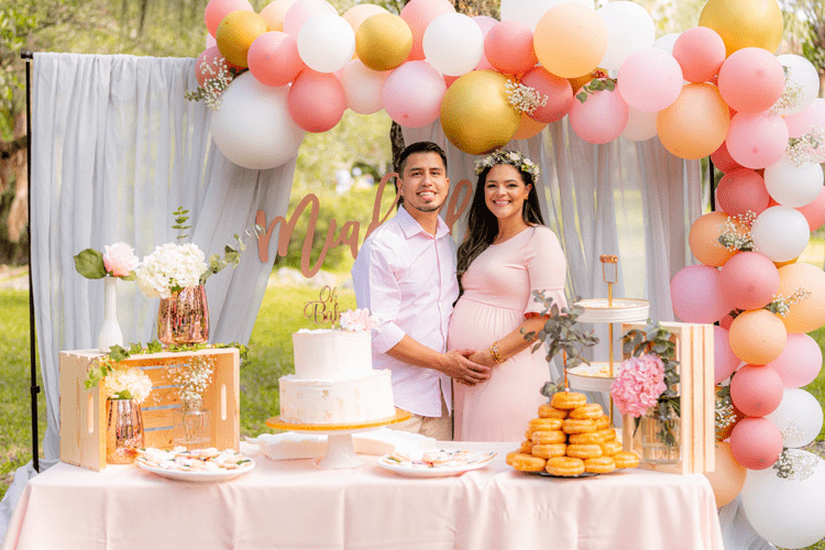 A couple having a pink-themed baby shower on a farm.