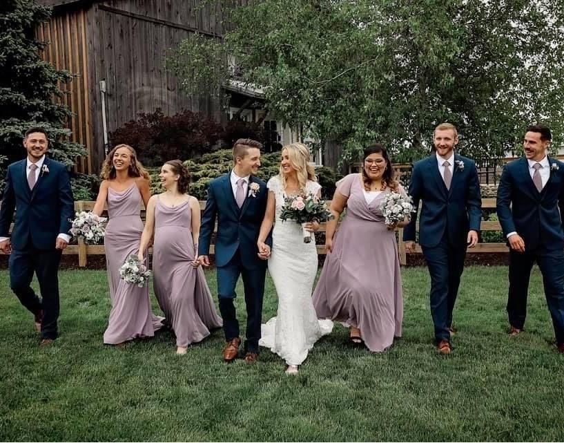 Bride, groom, groomsmen and bridesmaids exiting a barn