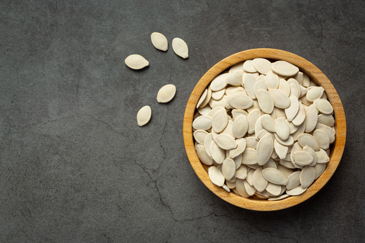 Pumpkin seeds laying out on a table and resting in a bowl.