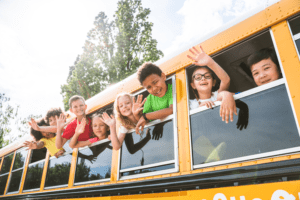 Students waving out the windows of a school bus.